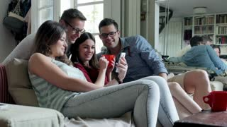 Friends watching something on smartphone and smiling to the camera