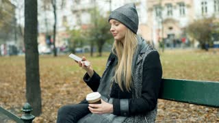 Girl answers cellphone and receives bad news while sitting in the autumnal park,
