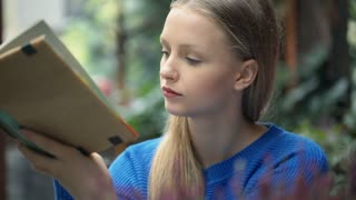 Girl answers cellphone while reading absorbing book, steadycam shot