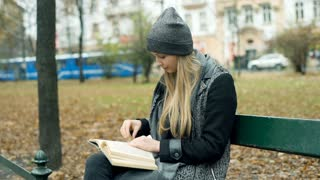 Girl answers cellphone while reading book in the autumnal park, steadycam shot