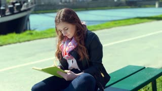 Girl answers cellphone while writing something in the notebook