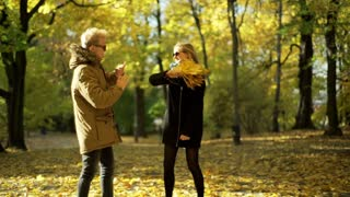 Girl beating her boyfriend with bunch of maple leaves