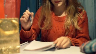 Girl checks the list with present in her notebook and packing them, steadycam sh
