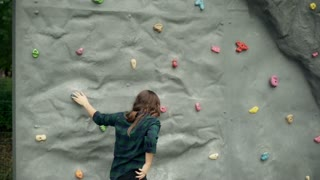 Girl climbing on the wall in the amusement park, steadycam shot