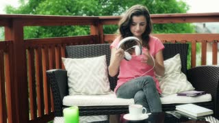 Girl connecting headphones to tablet and start listening music on patio