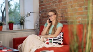 Girl covered by blanket sitting on the sofa and chatting on cellphone