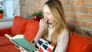 Girl crying while reading very emotional book on the couch