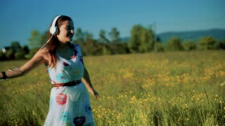 Girl dancing on the meadow and listening music on headphones