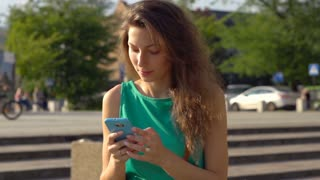 Girl dials number on cellphone and calling, steadycam shot, slow motion shot at