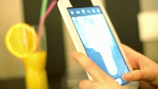 Girl doing photo of glass with orange juice on tablet