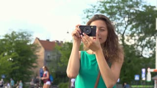 Girl doing photos on old camera in town, steadycam shot, slow motion shot at 240