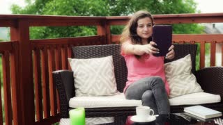 Girl doing selfie on tablet and sitting on terrace