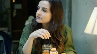 Girl drinking beverage in the cafe and looking around, steadycam shot
