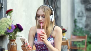 Girl drinking cocktail while listening music and browsing internet on smartphone