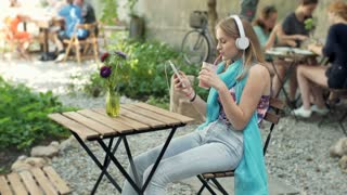 Girl drinking cocktail while listening music and using smartphone in the outdoor