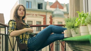 Girl drinking coffee on balcony and smiling to the camera