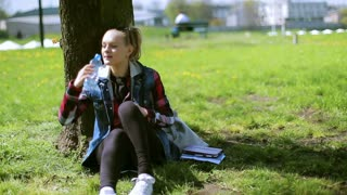 Girl drinking water in the park and smiling to the camera