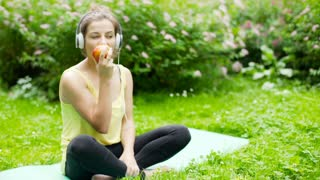Girl eating apple and listening music while sitting on exercising mat