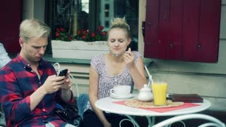 Girl eating mousse from coffee and boy using smartphone in the cafe