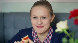 Girl eating sandwich and smiling to the camera in the cafe