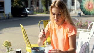 Girl eating yogurt in the outdoor cafe and smiling to the camera, steadycam shot
