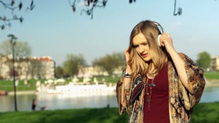 Girl finish listening music and standing in the park