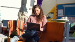 Girl finish using laptop while sitting outdoors and looking happy