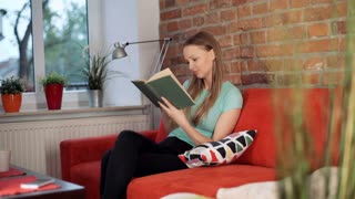 Girl finishes book and starts relaxing on the sofa