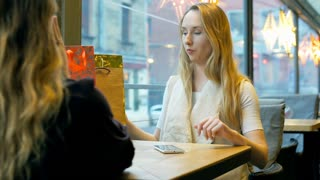 Girl giving present to her best friend in the festive cafe, steadycam shot