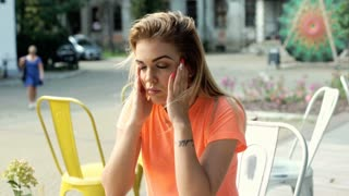 Girl having painful headache and taking pill while sitting in the outdoor cafe