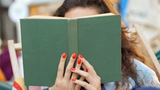 Girl hiding behind book and being flirtatious while smiling to the camera