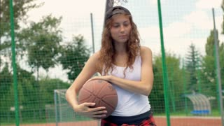 Girl holding ball and looking thoughtful while standing on the sports field