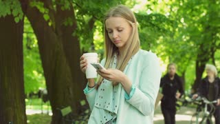 Girl holding cup of coffee and using smartphone while standing on pathway