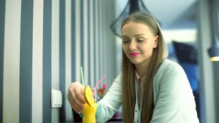 Girl holding glass with orange juice and smiling to the camera