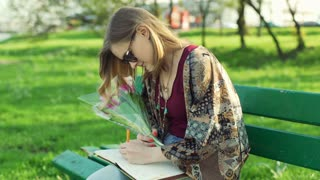 Girl holding tulips and writing thoughts in her diary