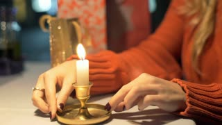 Girl holds burning candle and warms her hands in the cafe, steadycam shot