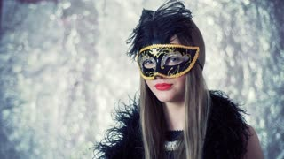 Girl in carnival mask and black scarf looking to the camera