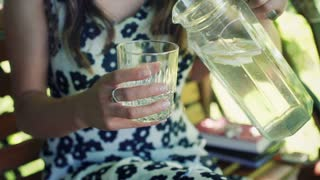 Girl in floral dress pouring water to the glass and drinking it