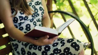 Girl in floral dress sitting on the bench and reading book