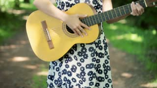 Girl in floral dress standing on pathway and playing on guitar