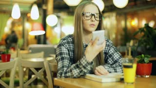 Girl in glasses and plaid shirt talking on cellphone while sitting in the cafe