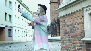 Girl in pastel jacket recording herself on the alley and going round