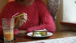 Girl in pink, fluffy sweater sitting in the cafe and eating delicious cake