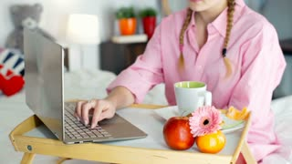 Girl in pyjamas sitting in the bed and typing something on laptop