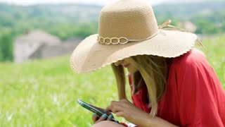 Girl in straw hat texting on smartphone while sitting on the meadow