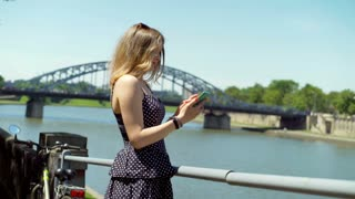 Girl in vintage dress standing next to the river and texting on smartphone