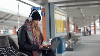 Girl in warm clothes listening music on headphones and using laptop