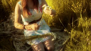 Girl kneel on the meadow and doing grommet from flowers
