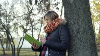 Girl leaning on tree in the park while doing notes and smiling to the camera