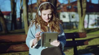 Girl listening music and browsing internet on tablet while sitting in the park